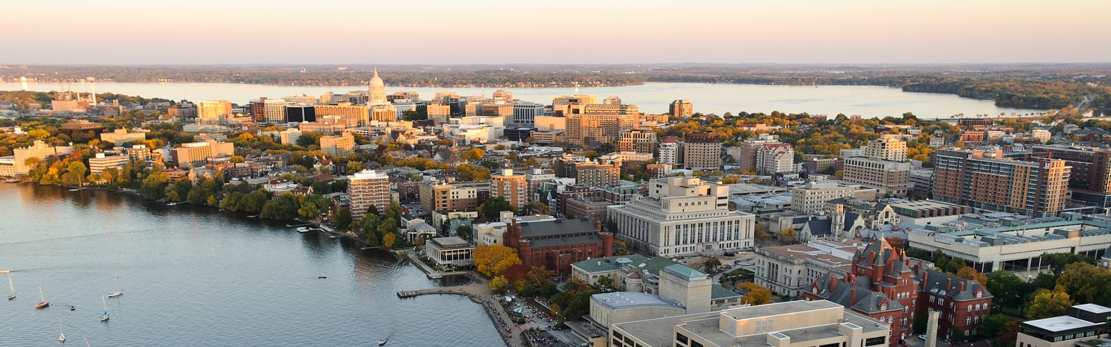 A wide shot of the Isthmus with the capitol building at the center. You can see the lakes on the bottom left and top right corners with a slight hint of morning daylight.